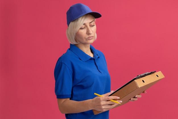 Donna di consegna bionda di mezza età sicura in uniforme blu e cappuccio che tiene il pacchetto di pizza matita per appunti guardando gli appunti