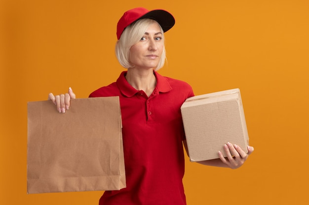 Donna di consegna bionda di mezza età sicura in uniforme rossa e cappuccio che tiene scatola di cartone e pacchetto di carta