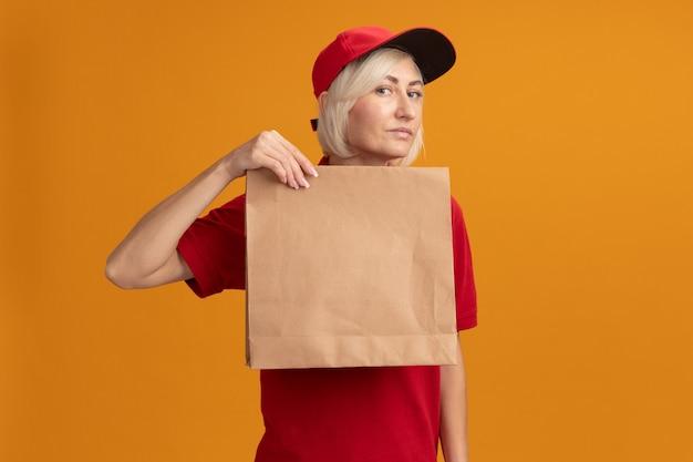 Donna di consegna bionda di mezza età sicura in uniforme rossa e cappuccio che tiene pacchetto di carta