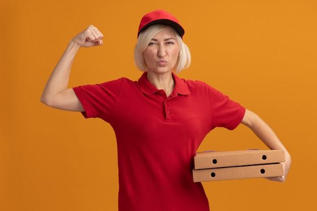 Fiduciosa donna bionda di mezza età in uniforme rossa e berretto che tiene in mano i pacchetti di pizza facendo un gesto forte con le labbra increspate