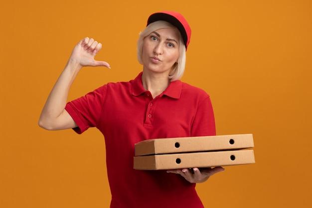 Donna di consegna bionda di mezza età sicura in uniforme rossa e berretto che tiene i pacchetti di pizza guardando davanti indicando se stessa con le labbra increspate isolate sul muro arancione