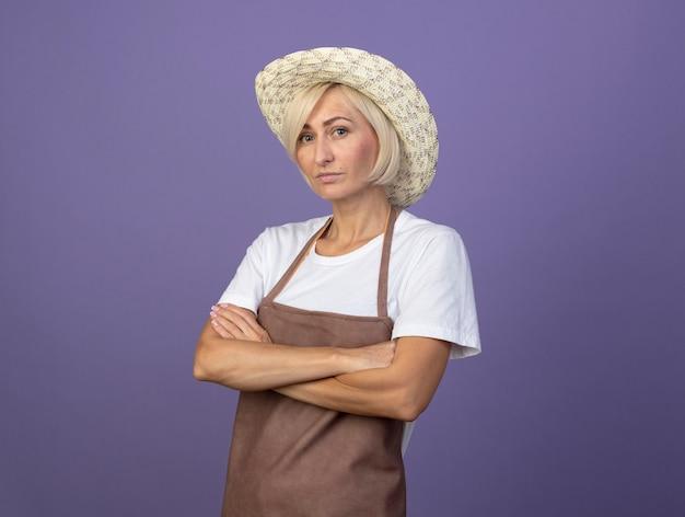 帽子をかぶって制服を着た自信を持って中年の金髪の庭師の女性