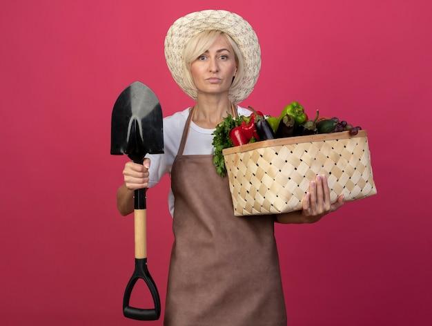 Fiducioso giardiniere biondo di mezza età donna in uniforme che indossa cappello con cesto di verdure e vanga