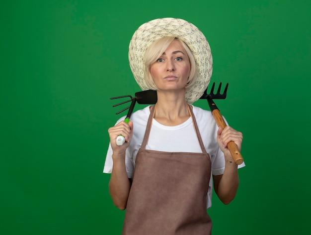 Fiducioso giardiniere biondo di mezza età donna in uniforme che indossa un cappello che tiene rastrello e zappa sulle spalle
