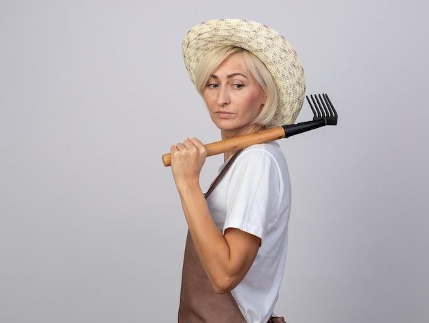 Fiducioso giardiniere biondo di mezza età donna in uniforme che indossa un cappello in piedi in vista di profilo tenendo il rastrello sulla spalla guardando a lato