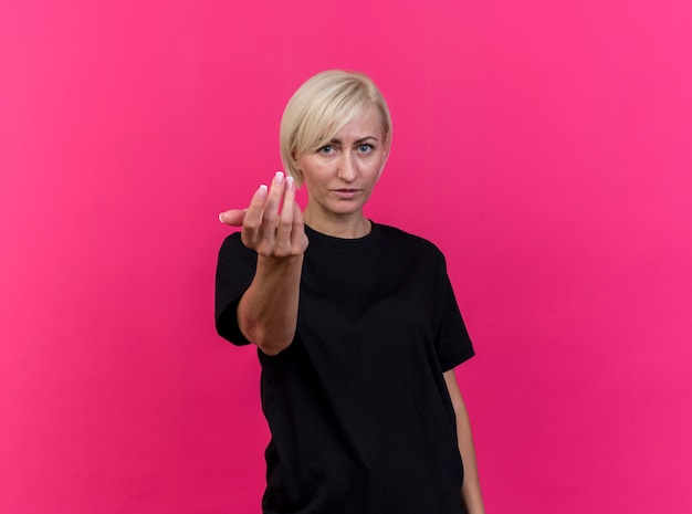 Уверенная белокурая славянская женщина средних лет делает жест, изолированные на малиновой стене с копией пространства