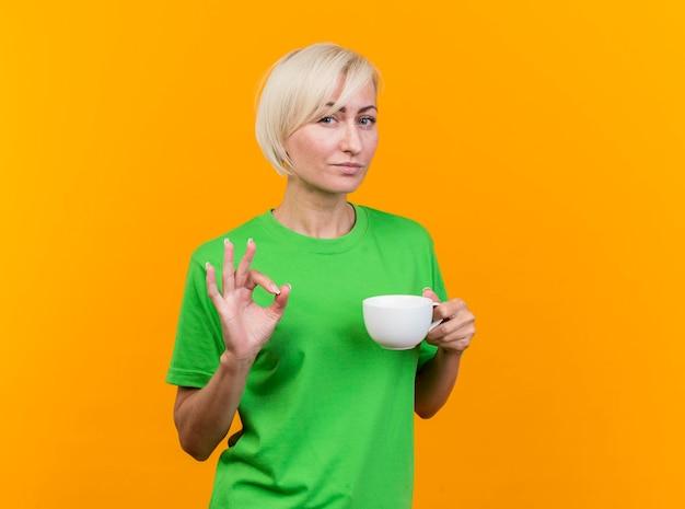 コピースペースと黄色の壁に分離されたokサインをやって正面を見てお茶を持っている自信を持って中年の金髪のスラブ女性