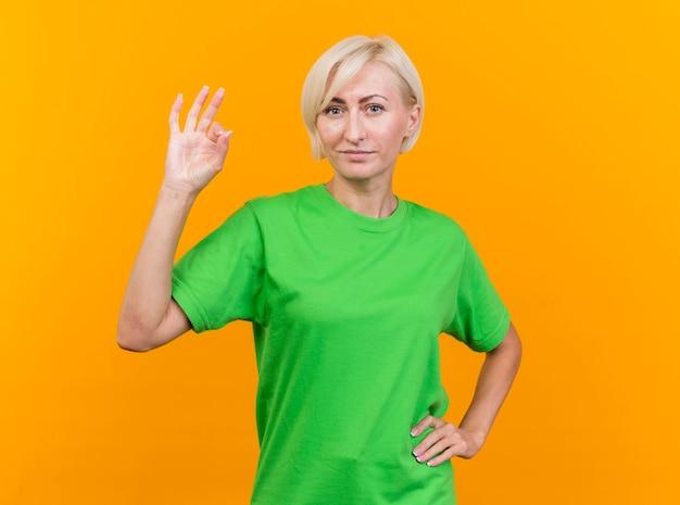 自信を持って中年の金髪のスラブの女性が前を見て腰に手を保ち、コピースペースで黄色の壁に分離されたokサインをやっています