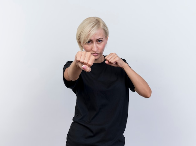 Confident middle-aged blonde slavic woman looking at camera doing boxing gesture isolated on white background with copy space