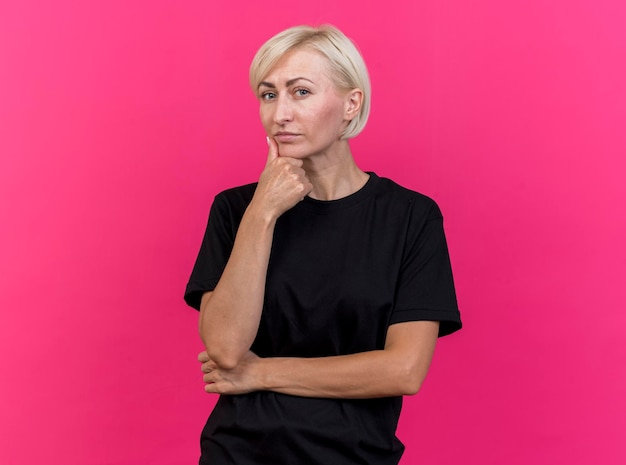Confident middle-aged blonde slavic woman looking at front touching chin isolated on pink wall with copy space