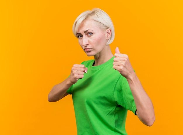 コピースペースで黄色の壁に分離されたボクシングのジェスチャーをしている正面を見て縦断ビューに立っている自信を持って中年金髪スラブ女性