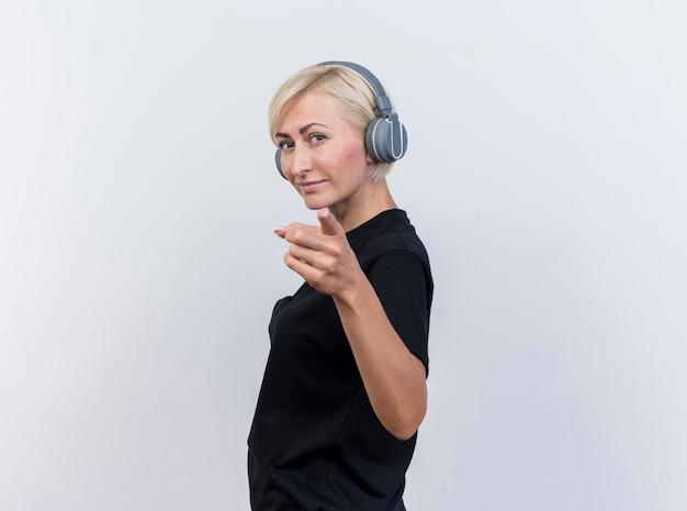 프로필보기에 서있는 헤드폰을 쓰고 자신감이 중년 금발 슬라브 여자를 찾고 복사 공간이 흰색 배경에 고립 된 카메라를 가리키는