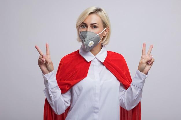 白い壁に分離された平和のサインを行う保護マスクを身に着けている赤いマントで自信を持って中年の金髪のスーパーヒーローの女性
