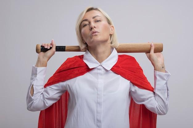 Donna bionda di mezza età sicura del supereroe in mantello rosso che tiene mazza da baseball dietro il collo