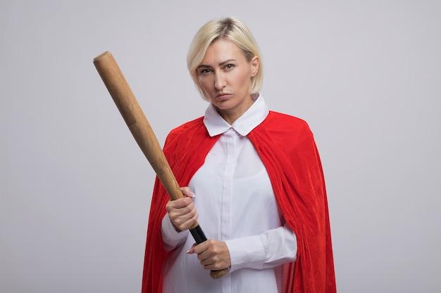 Donna bionda di mezza età sicura del supereroe in mantello rosso che tiene gli occhi strabici della mazza da baseball isolati sulla parete bianca con lo spazio della copia