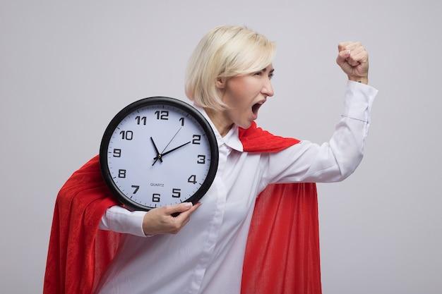 Donna bionda di mezza età sicura del supereroe in mantello rosso che tiene l'orologio che guarda il pugno alzato laterale