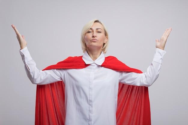 Donna bionda di mezza età sicura del supereroe in mantello rosso che tiene le mani in aria isolata sulla parete bianca