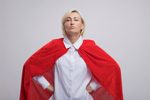 Confident middle-aged blonde superhero woman in red cape keeping hands on waist  isolated on white wall