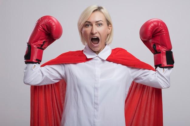 Fiduciosa bionda di mezza età supereroe donna in mantello rosso che indossa guanti box facendo un gesto forte urlando