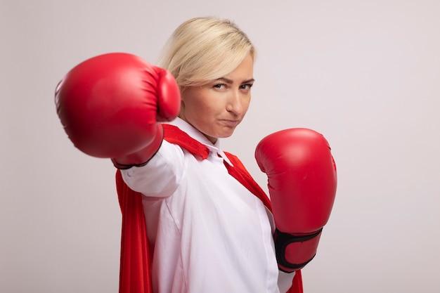Fiduciosa bionda di mezza età supereroe donna in mantello rosso che indossa guanti box allungando il pugno verso la telecamera