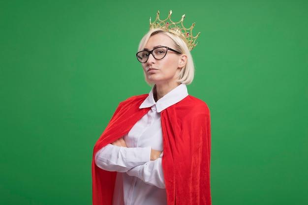 Fiduciosa bionda di mezza età supereroe donna in mantello rosso con gli occhiali e la corona in piedi con postura chiusa in vista di profilo