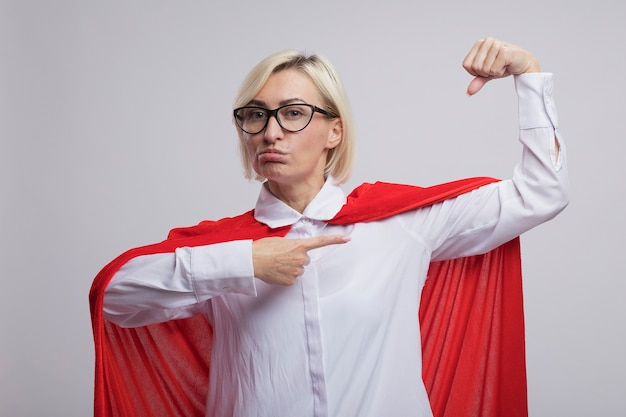 Confident middle-aged blonde superhero woman in red cape wearing glasses doing strong gesture pointing at her muscles