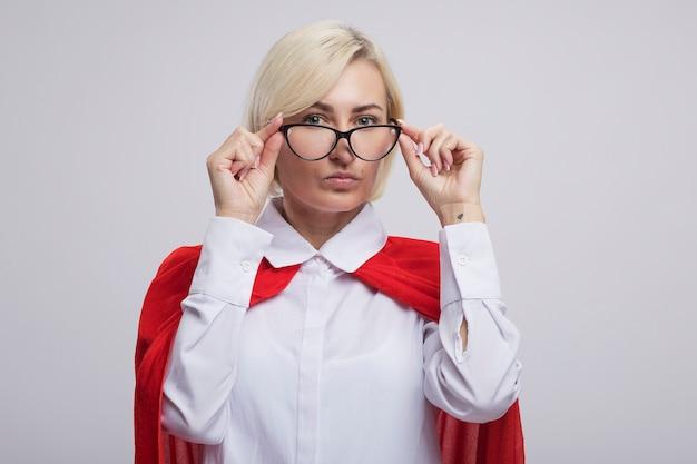 Fiduciosa bionda di mezza età supereroe donna in mantello rosso che indossa e afferra gli occhiali
