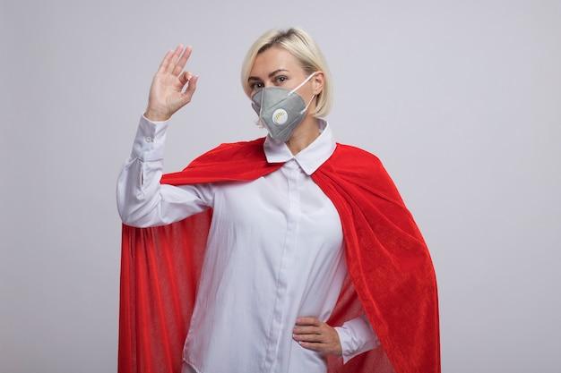 Donna supereroe bionda di mezza età sicura in mantello rosso che indossa maschera protettiva tenendo la mano sulla vita facendo segno ok isolato sul muro bianco con spazio di copia