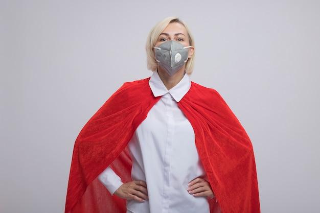 Fiduciosa donna bionda di mezza età supereroe in mantello rosso che indossa una maschera protettiva tenendo le mani sulla vita guardando la parte anteriore isolata sul muro bianco