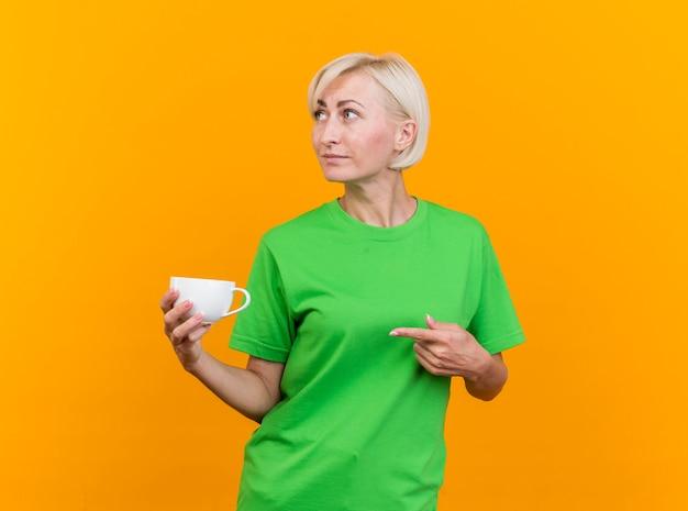 Donna bionda di mezza età sicura che tiene tazza di tè che osserva e che indica al lato isolato sulla parete gialla