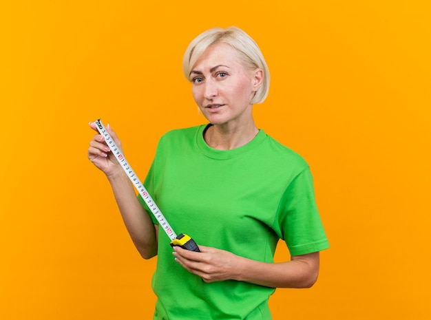 黄色の壁に隔離された巻尺を保持している正面を見て自信を持って中年のブロンドの女性