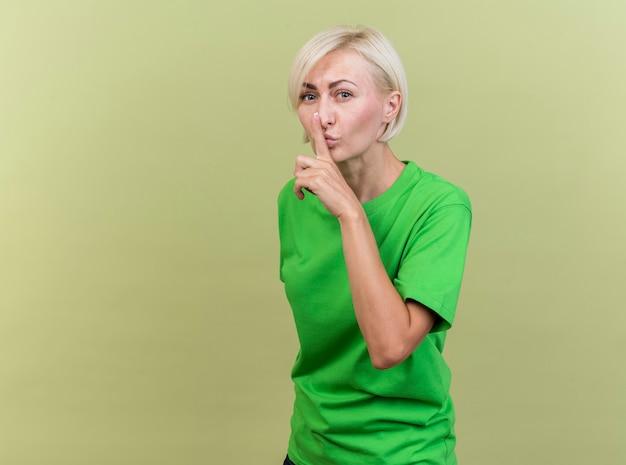 Donna bionda di mezza età sicura che sta nella vista di profilo che esamina la parte anteriore facendo il gesto di silenzio isolato sulla parete verde oliva