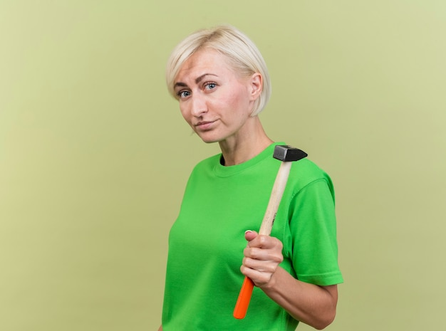 Confident middle-aged blonde woman standing in profile view looking at front holding hammer isolated on olive green wall
