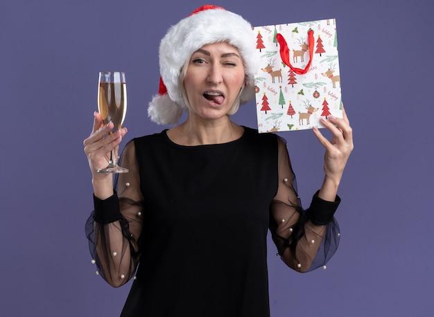 Donna bionda di mezza età sicura che porta il cappello di natale che guarda l'obbiettivo che tiene un bicchiere di champagne e toccare la testa con il sacchetto del regalo di natale che sbatte le palpebre e mostra la lingua isolata su sfondo viola