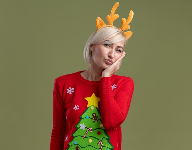 Confident middle-aged blonde woman wearing christmas reindeer antlers headband and christmas sweater looking  keeping hand on face doing kiss gesture isolated on olive green wall with copy space
