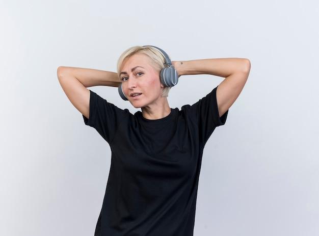 흰 벽에 고립 된 머리 뒤에 손을 유지 앞에보고 헤드폰을 착용 자신감 중년 금발의 여자