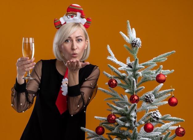 サンタクロースのカチューシャとネクタイを着た自信に満ちた中年の金髪の女性が、飾られたクリスマスツリーの近くに立ち、シャンパンのグラスを持って、オレンジ色の壁にブローキスを送る