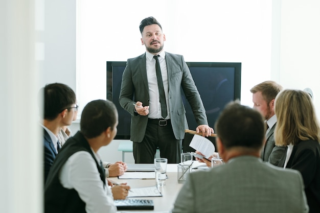 Confident middle aged businessman in formalwear standing by table in front of his colleagues and making report or speech at training