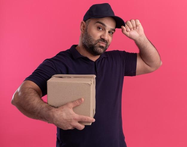 Уверенный доставщик средних лет в униформе и кепке, держащей коробку и кепку, изолированные на розовой стене