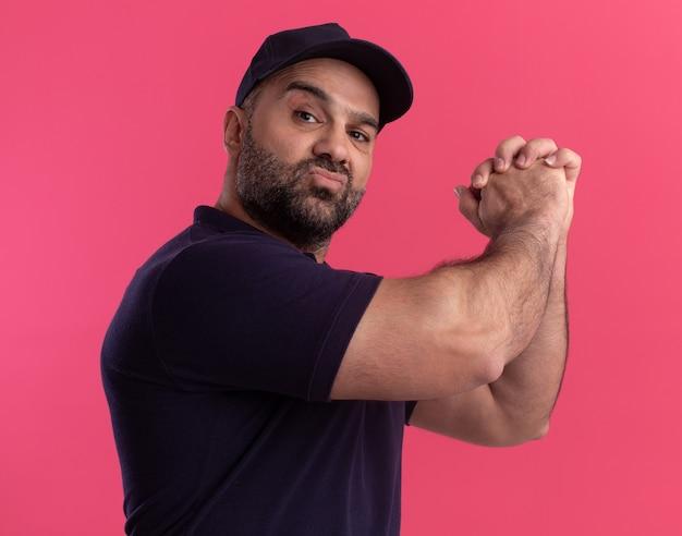 Уверенный доставщик средних лет в униформе и кепке, показывающий жест рукопожатия, изолированный на розовой стене