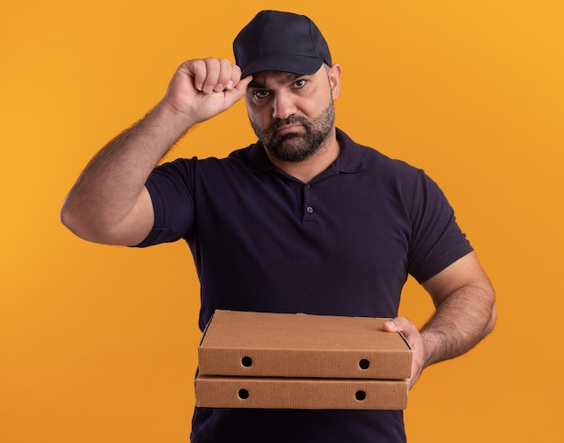 Confident middle-aged delivery man in uniform and cap holding pizza boxes and holding cap isolated on yellow wall