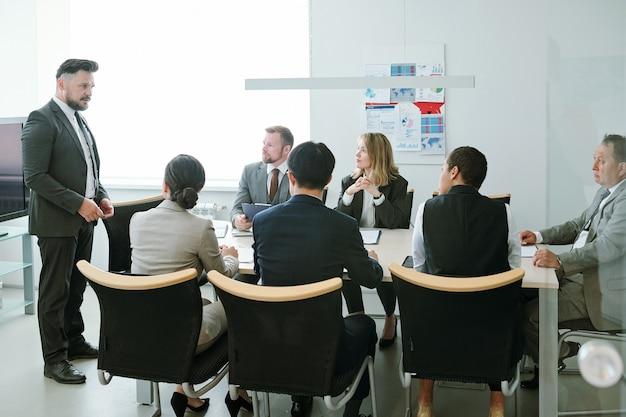Уверенный в себе директор деловой компании средних лет, стоящий перед своими подчиненными и выступающий во время обучения в зале заседаний