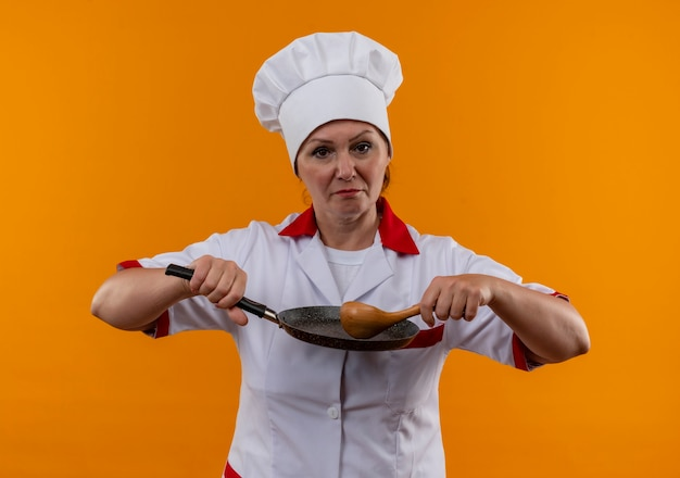 Confident middle-aged female cook in chef uniform holding frying pan and spoon on isolated yellow wall
