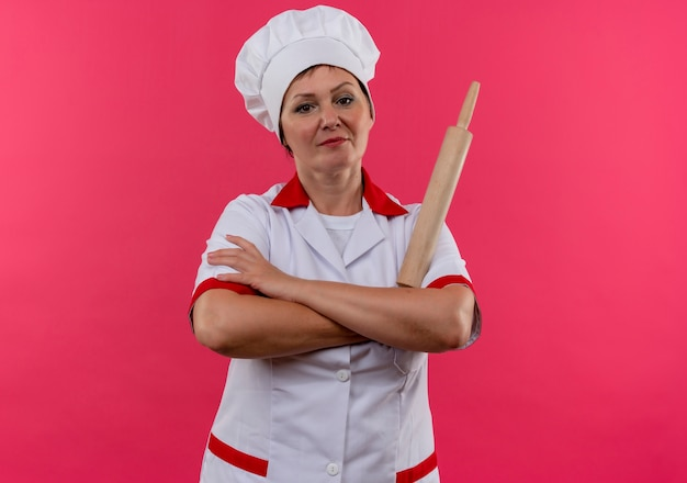 孤立したピンクの壁に麺棒交差手を保持しているシェフの制服を着た自信を持って中年女性料理人