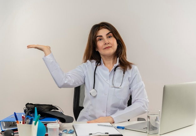 Medico femminile di mezza età sicuro che indossa veste medica e stetoscopio seduto alla scrivania con appunti di strumenti medici e laptop che mostra la mano vuota isolata