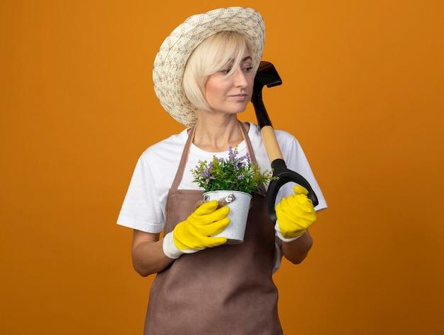 Fiducioso giardiniere di mezza età donna in uniforme da giardiniere che indossa cappello e guanti da giardinaggio tenendo vaso di fiori e vanga guardando a lato