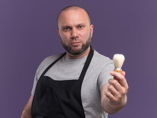 Уверенный в себе парикмахер средних лет в униформе, протягивая щетку для бритья перед камерой, изолированной на фиолетовой стене