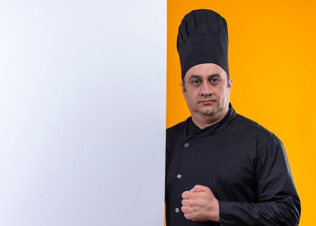 コピースペースと黄色の壁に白い壁を保持しているシェフの制服を着た自信を持って中年男性料理人