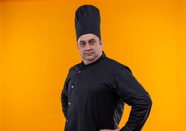 シェフの制服を着た自信のある中年男性料理人は、コピースペースのある黄色い壁に腰に手を置きます