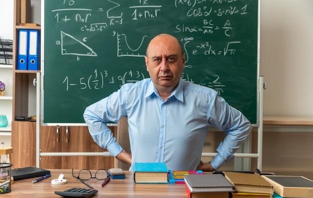 Fiducioso insegnante maschio di mezza età si siede al tavolo con materiale scolastico mettendo le mani sui fianchi in classe